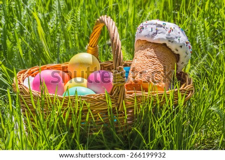 Wicker basket with painted eggs and Easter cake on the spring green grass - stock photo