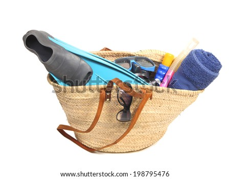 Wicker basket with towel, sunglasses, snorkel, flippers and suntan lotion - stock photo