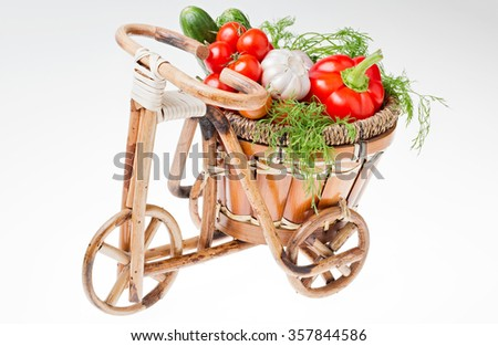 Wicker basket with vegetables : tomatoes, garlic, pepper, cucumber, dill  in the form of a Bicycle is harvest. Organic food. healthy Eating. The picture was taken on a white background. - stock photo