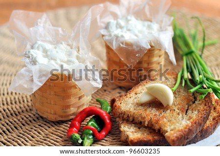 Wicker baskets with cottage cheese,  toasted bread and garlic - stock photo