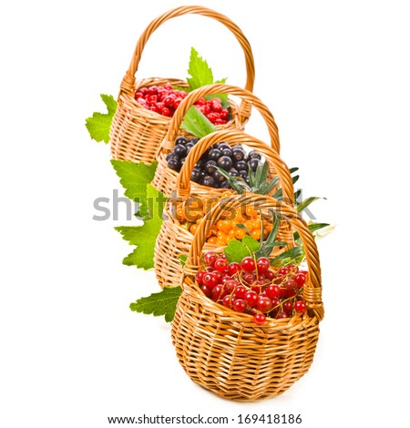 wicker baskets with various fresh berries, black currants, red currants, sea buckthorn isolated on white background - stock photo