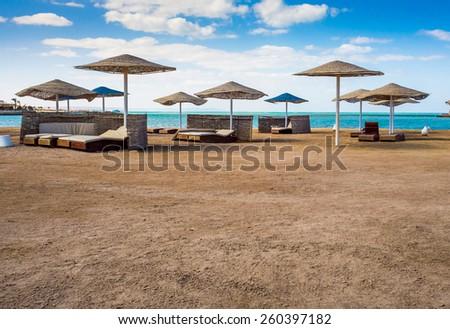 Wicker beach umbrellas on the beach. Beach chair on a tropical sand beach. Resort vacation on exotic beach of summertime. - stock photo