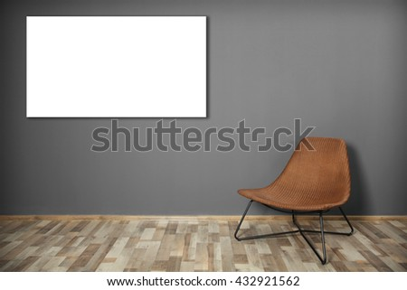 Wicker chair and picture frame on dark grey wall background