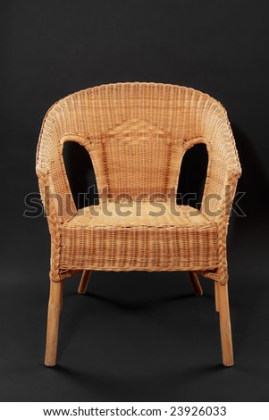 wicker chair over black background