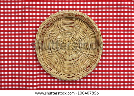 Wicker food basket on red and white checkered tablecloth - stock photo