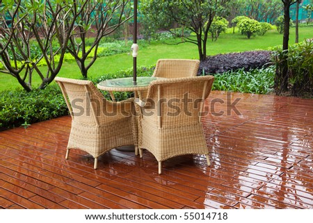 Wicker patio chairs and table near garden after raining - stock photo