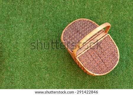 Wicker Picnic Basket On The Fresh Summer Grass Overhead View. Weekend Resting Concept - stock photo