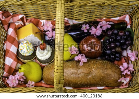 wicker picnic basket with fruits bread cheese cupcakes and wine spring flowers and red white checked table cloth  - stock photo