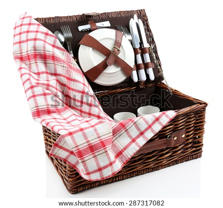 Wicker picnic basket with tableware and tablecloth isolated on white - stock photo