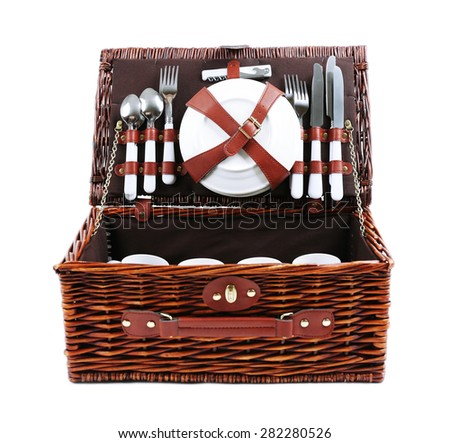 Wicker picnic basket with tableware isolated on white - stock photo