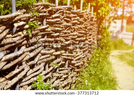 wicker rustic fence in the summer garden on grass background - stock photo