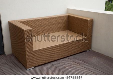 Wicker sofa in yard - stock photo