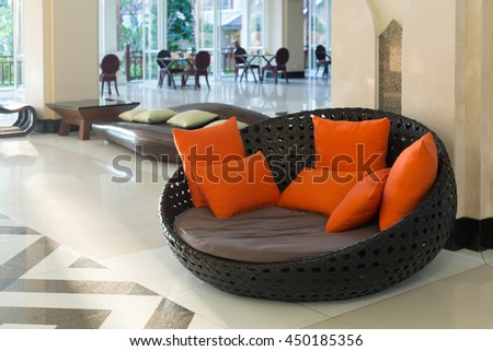 Wicker sofa with orange pillows in the lounge. - stock photo