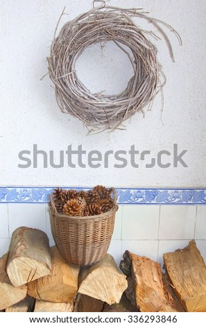 Wicker wreath, wicker basket, pine cones and wood blocks for the fireplace in the entrance hall of a home. On a background of antique blue tiles with lotus flowers. - stock photo