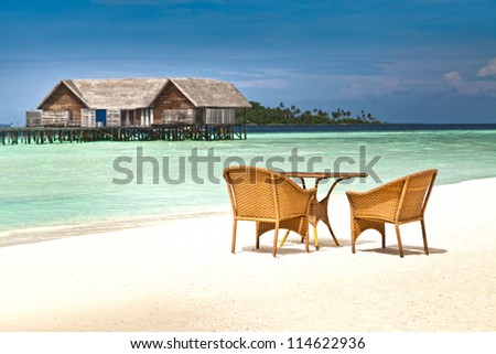 wickers chairs and table on the beach
