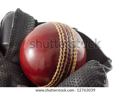 Wicket keeping glove with a new red cricket ball, isolated on white.