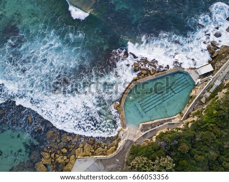Wide aerial view of Bronte rock pool with incoming waves