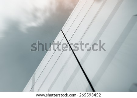 Wide angle abstract background view of steel light blue high rise commercial building skyscraper made of glass exterior. concept of successful industrial architecture and office center building