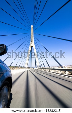 Wide angle driving over a bridge at high speed. Focus on bridge tower. - stock photo