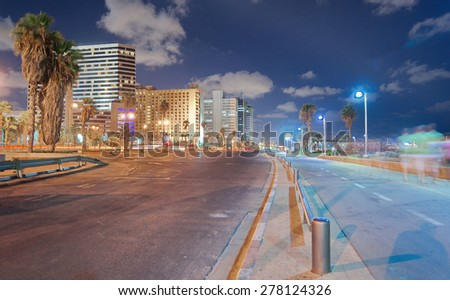 Wide angle long exposure view of the Tel Aviv, Israel beach promenade  at night with blurred people and riders, and towers in the background. - stock photo