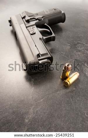 Wide angle of handgun with muzzle and two hollow point bullets. - stock photo