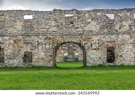 Wide angle old ruins built with stone bricks and overgrown with plants, with a gate with an arc in the center and numerous window holes giving view across the ruins - stock photo