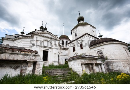 Wide angle photo of an old christian church in Staricy, Russia. Vintage religious building with dramatic cloudy sky.  - stock photo