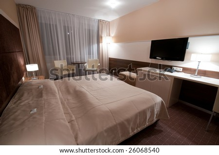 wide angle picture of interior hotel room - huge bed for two with flat TV in front