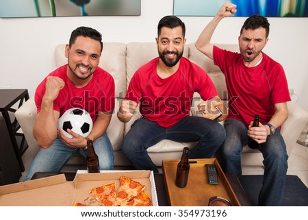 Wide angle portrait of three male friends and soccer fans celebrating a goal and a victory while watching the game on TV - stock photo