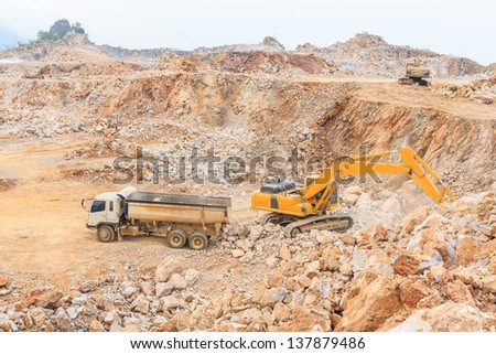 wide angle shot excavator loading crushed rock on  dumper truck at dolomite mines site - stock photo