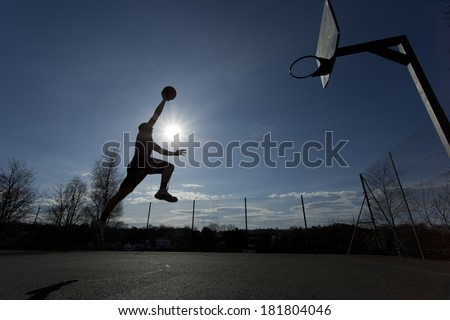 Wide angle shot of a basketball player silhouette taking off towards slam dunking the ball - stock photo
