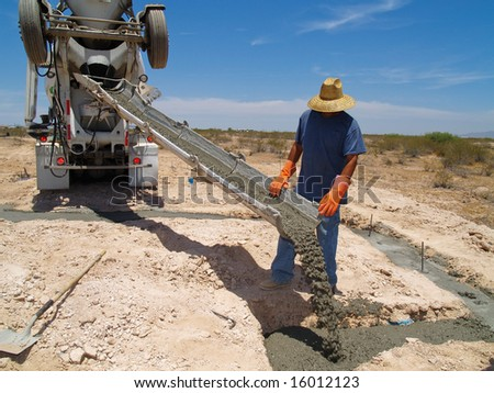 Wide angle shot of a construction worker directing cement from a mixing truck into a foundation. Horizontally framed shot.