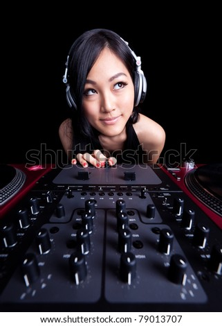 Wide angle shot of a female DJ using the crossfader of a mixer - stock photo