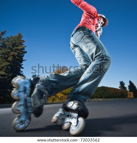 Wide-angle shot of a sliding rollerskater - strong motion blur on person - stock photo