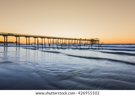 Wide angle shot of Scripps Pier with reflection during sunset in La Jolla, San Diego, California - stock photo