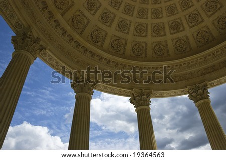 Wide-angle view from below showing details of the cupola of the Temple of Love in Marie-Antoinette's Estate in Versailles, Paris, France, including four Corinthian columns, sky and clouds