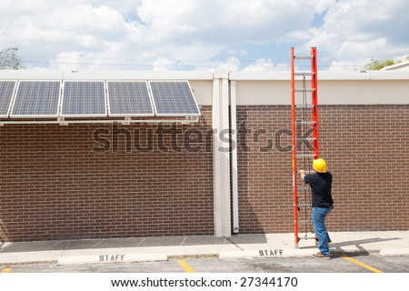 Wide angle view of a construction worker preparing to climb on to the roof of a building to work on solar panels. - stock photo
