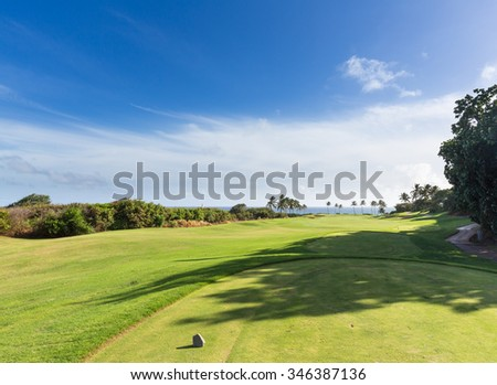 Wide angle view of a golf tee marker on fairway of golf course overlooking ocean near Lihue, Kauai