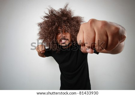 Wide angle view of a man with funky hairstyle giving a punch