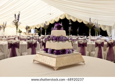 Wide angle view of a wedding cake with venue in background, slightly out of focus - stock photo