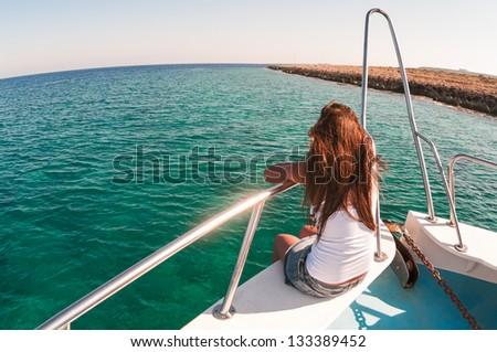 Wide angle view of back sitting woman on shipboard with legs out. Copyspace - stock photo