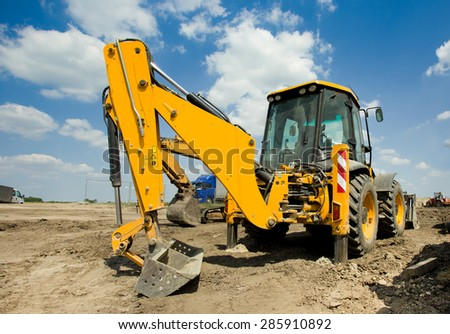 Wide angle view of excavator standing on ground with blue sky and white clouds in background - stock photo