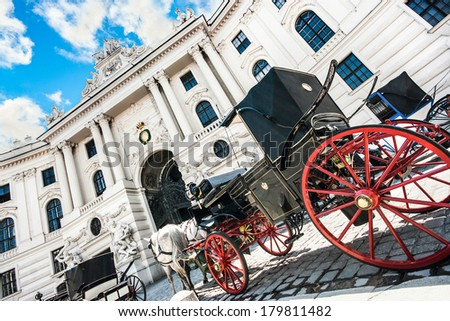 Wide-angle view of famous Hofburg Palace with traditional horse-drawn Fiaker carriages on a sunny day in Vienna, Austria - stock photo