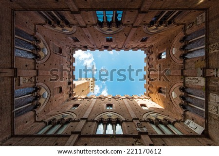 Wide angle view of famous Torre del Mangia at Palazzo Pubblico in Siena, Italy - stock photo