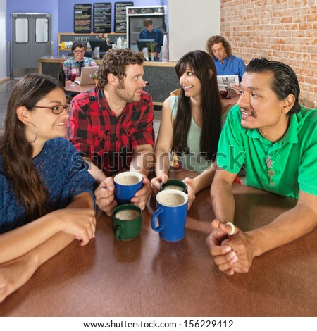 Wide angle view of four people talking in a coffee house - stock photo
