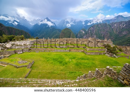 Wide angle view of Machu Picchu, Peru with a row and Andes Mountains in the background - stock photo