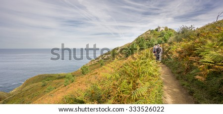 Wide angle view of mountain with Lighthouse in the coast of San Sebastian with cargo ship and tourists, Spain - stock photo