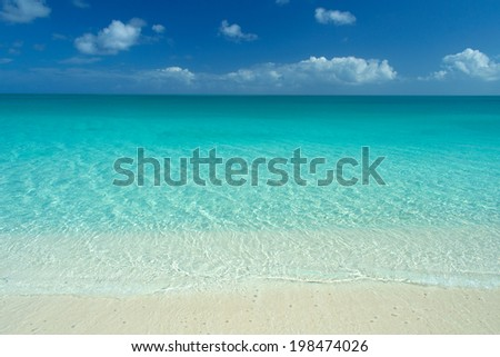wide angle view of perfect caribbean white sand beach, turquoise waters and blue sky - stock photo