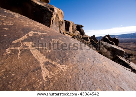 Wide angle view of petroglyphs carved onto rock surface by prehistoric Native American(s) at Anasazi Canyon, southern Utah desert, USA. - stock photo