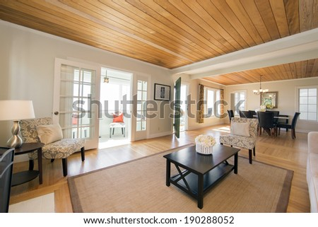 Wide angle view of spacious sitting area of modern sumptuous style  living room with wooden ceiling and floors. - stock photo